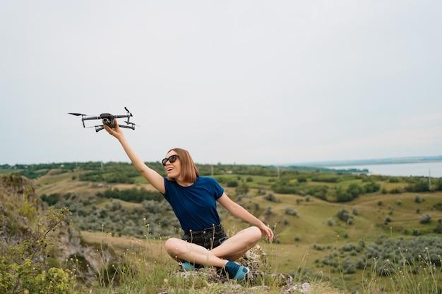 Uma mulher caucasiana com um drone na mão, sentado em uma colina rochosa verde com céu no fundo