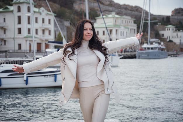 Uma mulher caucasiana despreocupada em roupas bege, apreciando a vista do mar em um dia quente e ventoso