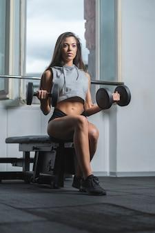 Uma mulher caucasiana em forma fazendo levantamento de bíceps com pesos em uma academia. ela é forte e determinada. ela está sentada em um banco. ela está vestindo roupas esportivas escuras. ela está olhando para longe