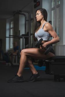 Uma mulher caucasiana em forma fazendo levantamento de bíceps com pesos em uma academia. ela é forte e determinada. ela está sentada em um banco