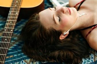 Uma mulher caucasiana está ouvindo música