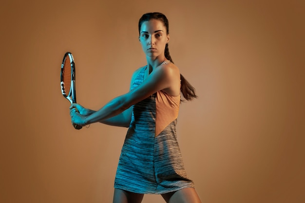 Uma mulher caucasiana jogando tênis isolado em um fundo marrom em luz mista e néon. ajuste a jovem jogadora em movimento ou ação durante o jogo de esporte. conceito de movimento, esporte, estilo de vida saudável.