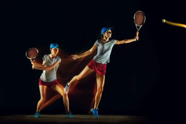 Uma mulher caucasiana jogando tênis isolado na parede preta em luz mista e stobe. ajuste a jovem jogadora em movimento ou ação durante o jogo de esporte. conceito de movimento, esporte, estilo de vida saudável.