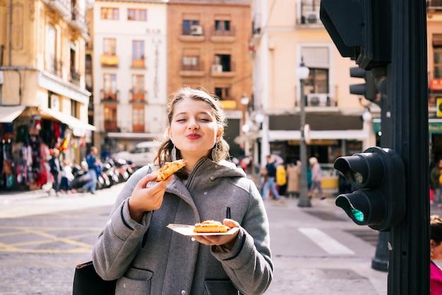 Uma mulher caucasiana loira feliz come pizza em uma rua da cidade