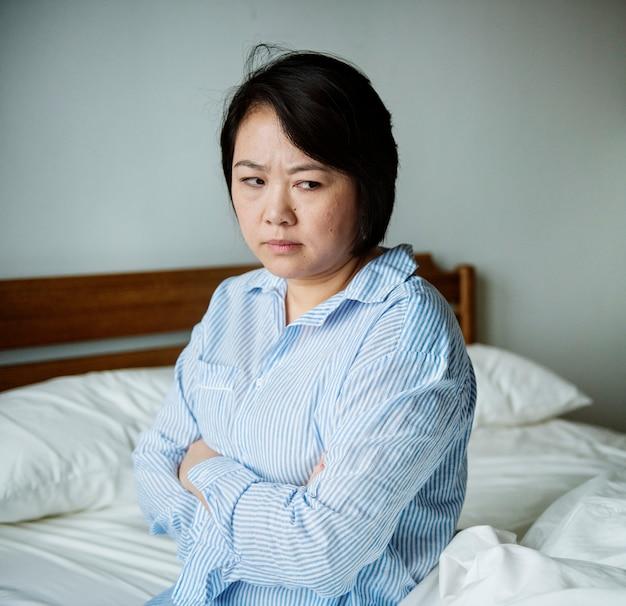 Uma mulher chateada em um quarto de cama