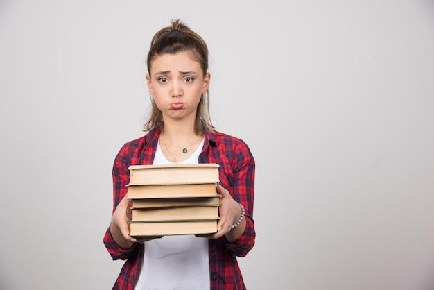 Uma mulher chateada mostrando uma pilha de livros em uma parede cinza