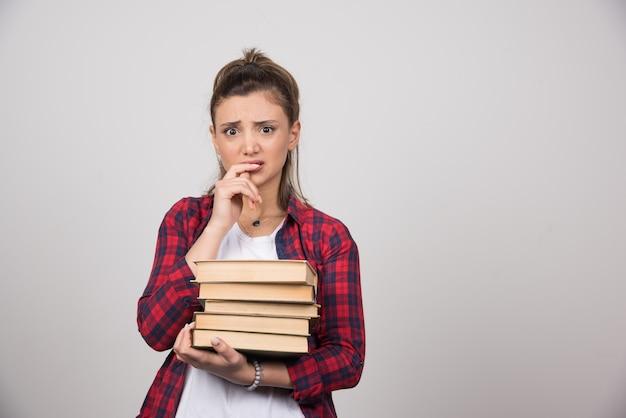 Uma mulher chateada segurando uma pilha de livros em uma parede cinza.