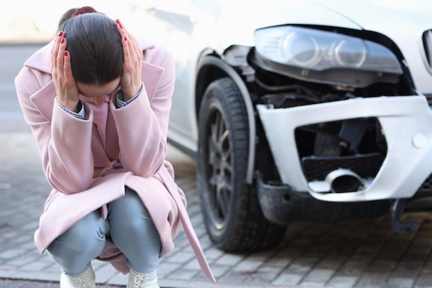 Uma mulher chateada senta-se com a cabeça baixa ao lado de um carro revelado