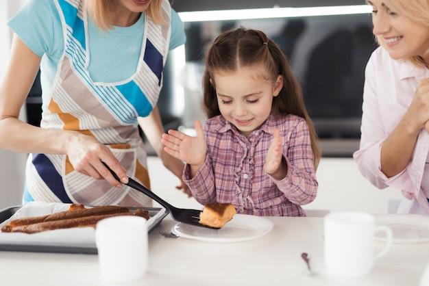 Uma mulher coloca um pedaço de bolo para sua filha.