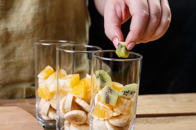 Uma mulher coloca um pedaço de kiwi em um copo de frutas para um coquetel de frutas.