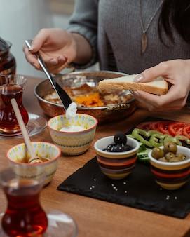Uma mulher colocando creme em uma fatia de pão em torno de uma mesa de café da manhã com muitos alimentos.