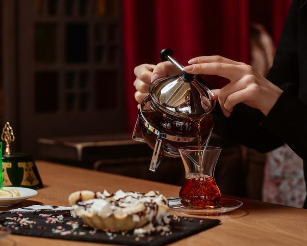 Uma mulher colocando um copo de chá na mesa de chá com doces