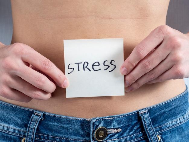 Uma mulher com a barriga nua segura um adesivo de papel com a inscrição - estresse com as duas mãos. o conceito de gravidez e a posição da mulher na sociedade
