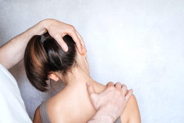 Uma mulher com ajuste de pescoço quiropraxia. osteopatia, cinesiologia, correção de má postura