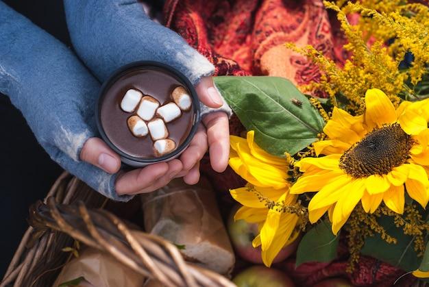 Uma mulher com as mãos nas luvas segurando uma caneca de chocolate quente ou chocolate quente