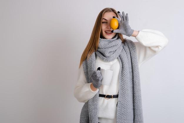 Uma mulher com cabelos longos tem uma caneca e limão nas mãos. estação do outono.