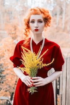 Uma mulher com cabelos ruivos e um vestido justo vermelho com um buquê de flores amarelas na mão.