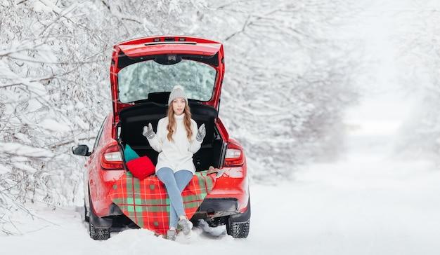 Uma mulher com café quente nas mãos está sentada em um carro vermelho em um dia nevado de inverno na floresta.