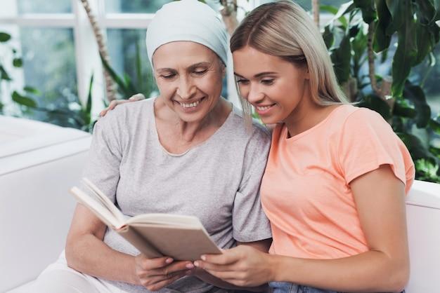 Uma mulher com câncer está sentada ao lado de sua filha.