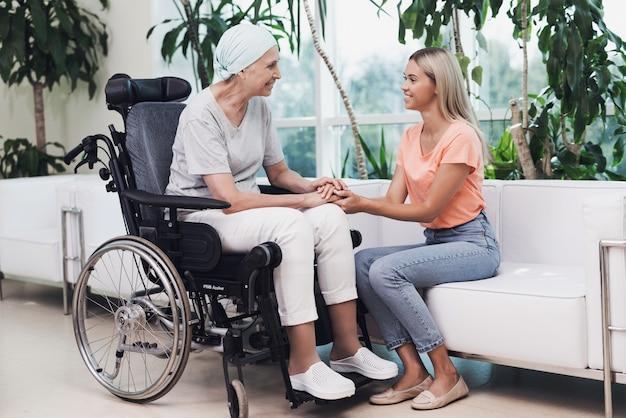 Uma mulher com câncer está sentado em uma cadeira de rodas