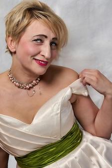 Uma mulher com decote profundo abaixa a alça do vestido no ombro