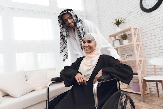 Uma mulher com deficiência em um hijab está sentado em uma cadeira de rodas.