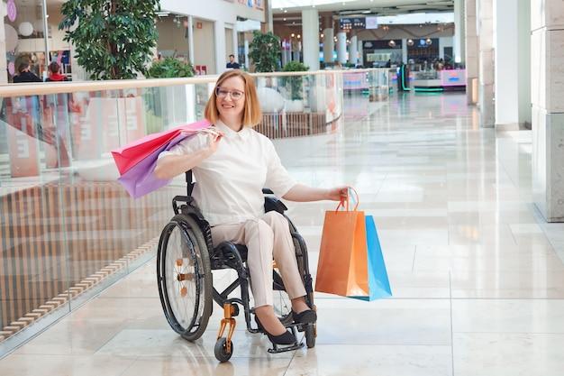 Uma mulher com deficiência usando um chapéu de papai noel em uma liquidação de natal em um shopping