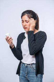Uma mulher com dor na mão segura um frasco de remédio e a outra mão, mas na cabeça