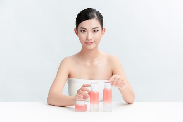 Uma mulher com frascos de cosméticos na mesa