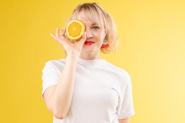 Uma mulher com laranjas nos olhos. lábios de batom vermelho. menina alegre e alegre exala laranjas positivas e mimadas. isolado em fundo amarelo