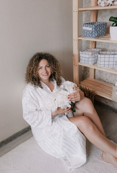 Uma mulher com lindos cabelos cacheados está sentada no chão, com uma túnica branca, segurando um buquê de peônias nas mãos. mulher feliz
