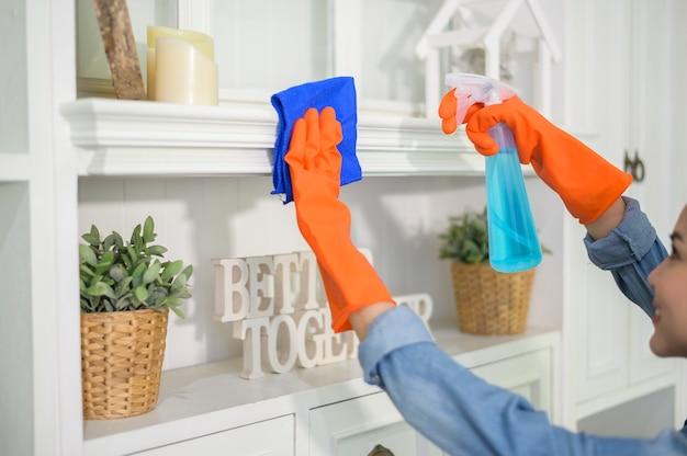 Uma mulher com luvas de limpeza usando álcool em spray desinfetante para limpar a casa, saudável e médica, conceito de proteção covid-19 em casa.