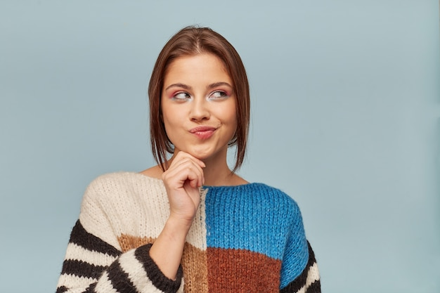 Uma mulher com maquiagem brilhante, cabelo preso atrás olha pensativamente para o canto superior direito segura um punho perto do queixo
