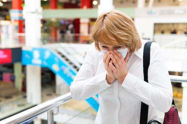 Uma mulher com máscara de vírus anda por um local público da cidade.