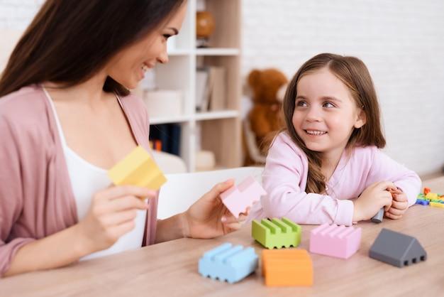 Uma mulher com menina está construindo um bloqueio de cubos de madeira.