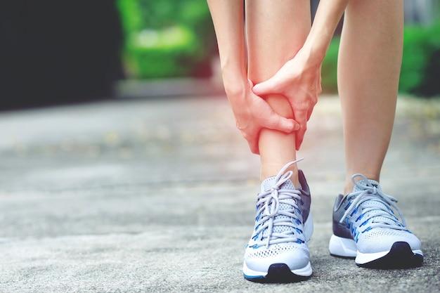 Uma mulher com muita dor na perna no parque