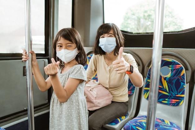 Uma mulher com o polegar para cima e uma menina com um gesto com a mão simbolizam o amor ao usar uma máscara no ônibus durante a viagem