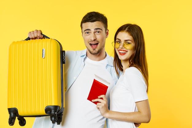 Uma mulher com passaporte e passagens está ao lado de um homem com uma mala de viagem