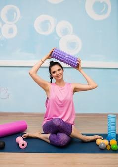 Uma mulher com roupas esportivas está sentada com bolas de massagem em um tapete no estúdio