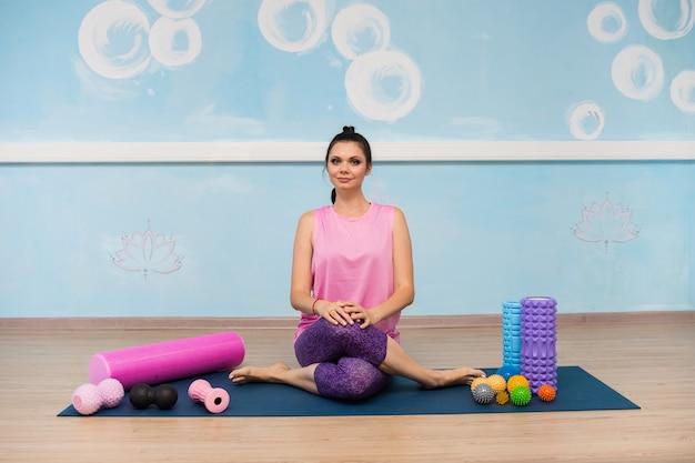 Uma mulher com roupas esportivas está sentada em um tapete com massageadores ortopédicos