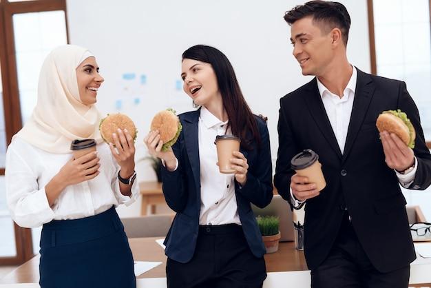 Uma mulher com seus colegas comendo um hambúrguer.