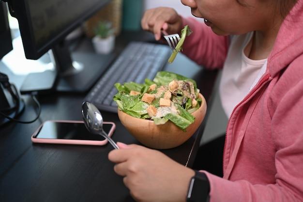 Uma mulher com sobrepeso comendo uma salada e tentando perder peso.