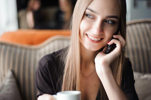 Uma mulher com sorriso fofo tendo conversa por telefone móvel