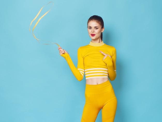 Uma mulher com um agasalho elegante pratica esportes e faz exercícios, um agasalho amarelo, espaço azul
