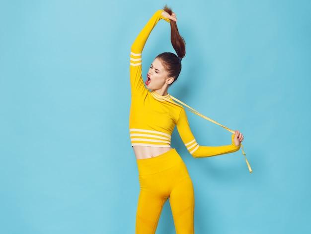 Uma mulher com um agasalho elegante pratica esportes e faz exercícios, um agasalho amarelo, superfície azul