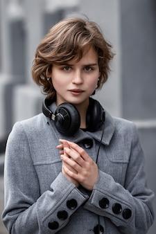 Uma mulher com um casaco cinza e fones de ouvido