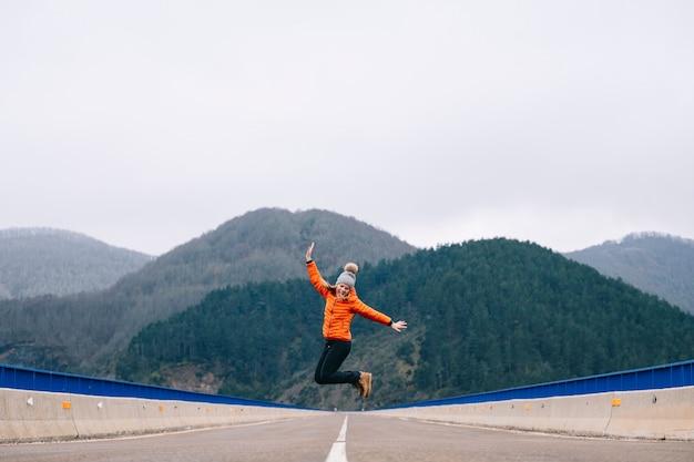 Uma mulher com um chapéu de lã e casaco laranja caminha corre e pula por uma estrada com montanhas ao fundo