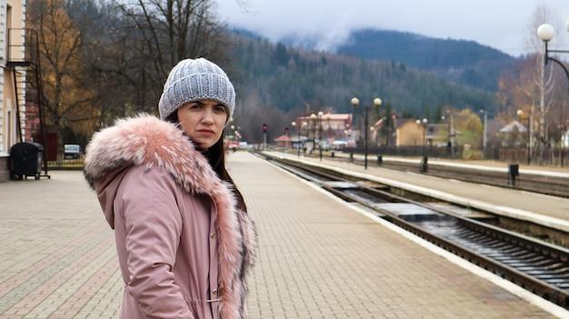 Uma mulher com um chapéu de malha cinza e uma jaqueta rosa com pele espera o trem na estação para ver o trem que chega. transporte ferroviário. conceito de viagens outono e inverno.