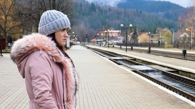 Uma mulher com um chapéu de malha cinza e uma jaqueta rosa com pele espera o trem na estação. transporte ferroviário. conceito de viagens outono e inverno.