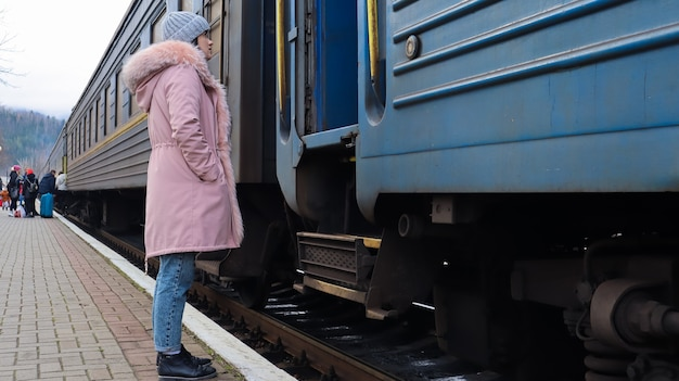 Uma mulher com um chapéu de tricô cinza e uma jaqueta rosa com pele entra no vagão de um velho trem na estação. transporte ferroviário. conceito de viagens outono e inverno. transporte ferroviário.